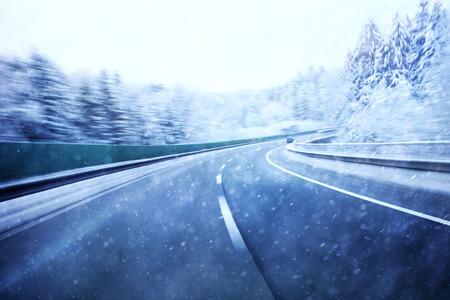 peligro: Dangerous borrosa conducir en invierno carretera. Invierno condiciones de nieve en la carretera. El desenfoque de movimiento visualizies la velocidad y la dinámica. Foto de archivo