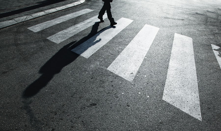 Dangerous road crossing with pedestrian feet and shadow. Concept safety. Stock Photo