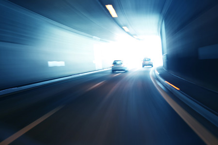 Blurry silver blue color tunnel high speed car driving. Motion blur visualizies the speed and dynamics.