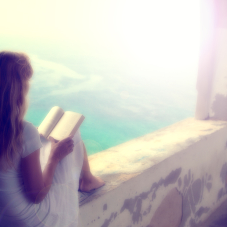 Relaxed blurry blonde woman reading a book outside. Light filter effect added.