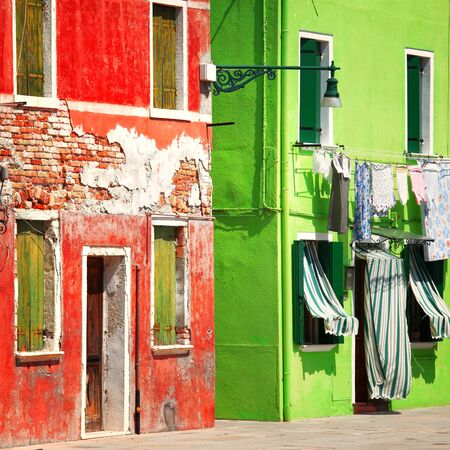 Colorful detail of old red and green house facades taken on Burano island , Venice, Italy.