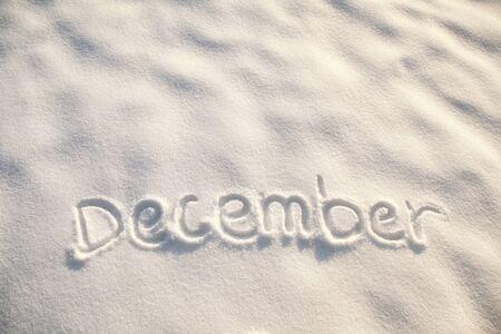 December Month word handwriting on fresh snow.