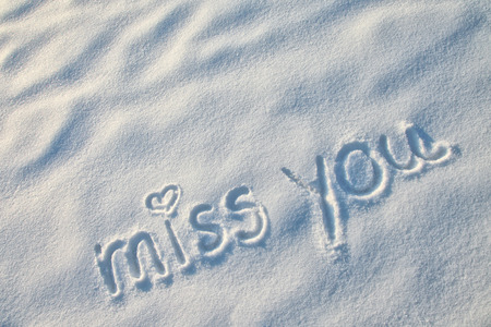 miss you: Miss you with heart sign writing on the snow. Stock Photo