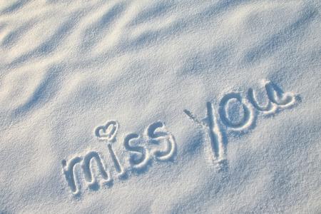 Te echo de menos con la muestra del coraz�n escrito en la nieve. Foto de archivo