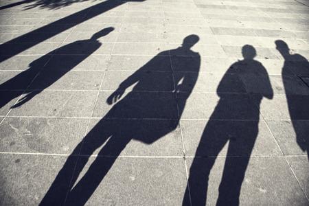 Las personas ocupadas sombras en calle pavimentada de la ciudad en un d�a soleado. La gente camina por la calle.