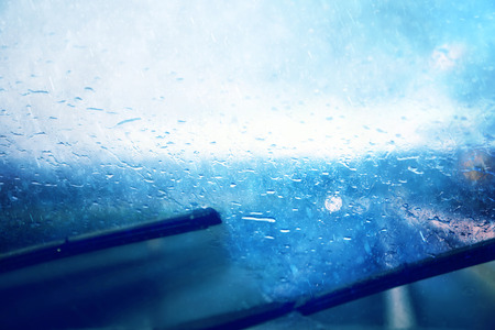 dangerous: Dangerous vehicle driving in the heavy rainy and slippery road. Raindrops on windshield of moving car on highway. Blue color tone used.