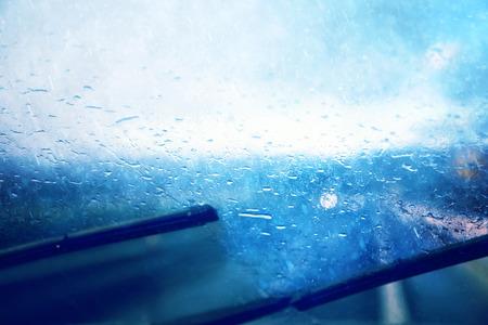 peligro: Vehículo peligroso conducir en la carretera de lluvias y resbaladizo pesado. Gotas de agua en el parabrisas del coche en movimiento en la carretera. Tono de color azul utilizado. Foto de archivo