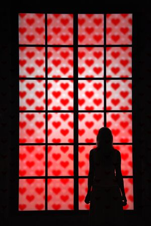 lonely heart: Lonely women in love looking through big closed glass window with red heart signs and thinking about love things. Conceptual Valentine Holiday background with women in love silhouette. Stock Photo