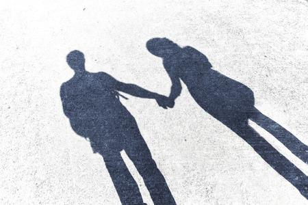 로맨스: 산책에 사랑에 부부의 그림자. 거리에서 손을 잡고 남성과 여성의 그림자. 그런 지와 대비 필터 효과를 사용합니다. 스톡 콘텐츠