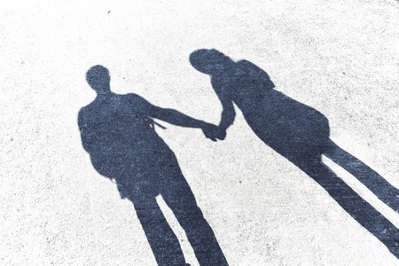 the season of romance: Shadows of couple in love on a walk. Shadow of men and women holding hands on the walk. Grunge and contrast filter effect used.