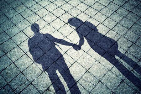 personas saludandose: Sombras del Grunge de pareja en el amor en un suelo de piedra de la ciudad. Sombra de los hombres y mujeres que llevan a cabo las manos. De color turquesa y el efecto de viñeta utilizan.