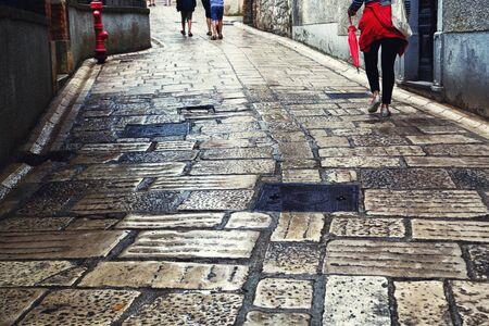 empedrado: La gente ocupada caminando en una calle pavimentada de la ciudad húmeda en el día lluvioso.