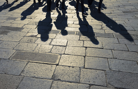 Shadows of group of people walking through the streets at morning sunlight. Silhouette of group people walking.