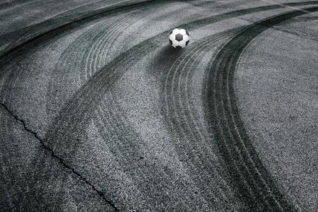 Soccer ball with shadows on a dangerous road. Abstract asphalt road with illustrated soccer ball background.