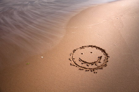 해변 모래에 웃는 기호. 흐릿한 파도를 만드는 데 사용되는 중립 밀도 필터. 스톡 콘텐츠