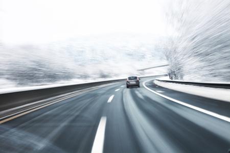 frenos: A su vez rápido borrosa en la carretera de nieve helada con un coche en el primer plano. el desenfoque de movimiento visualizies peligro de la alta velocidad y la dinámica.