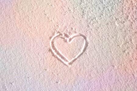 신선한 눈 속에서 사랑스러운 필기 심장 모양입니다. 보라색 노란색 빛의 마법의 겨울 심장 모양 배경. 스톡 콘텐츠