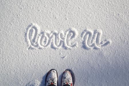 필기 사랑 당신에게 단어와 함께 신선한 눈으로 덮여 눈 덮인 필드에 서있는 빨간 신발 사람. 사랑하면 메시지와 함께 눈 덮인 필드에 서있는 한 사람 스톡 콘텐츠