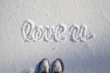 Person with red shoes standing on snowy field, covered with fresh snow with handwritten love you words. Point of view of  one person standing on a snowy field with love you message.