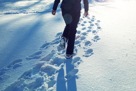 맑은 날에 눈 덮인 시골 필드에 산책하는 외로운 여자.