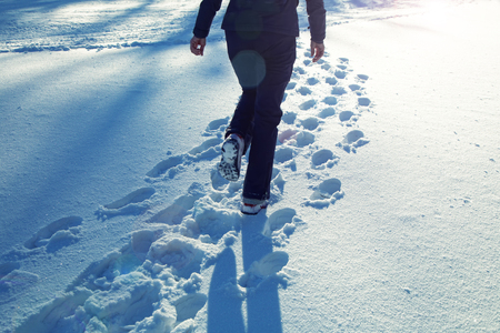Lonely woman walking in the snowy countryside field at sunny day.