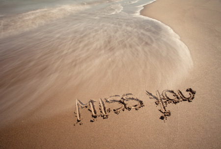 Miss you handwriting sign on sea sand with wave. Neutral densitiy filter used to make blurry waves.