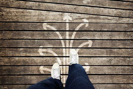 selections: Man foot shoes from an aerial view on aged wooden floor with arrows direction selections background. Conceptual point of view man walking on textured wooden floor with place for text message and with arrows set. Stock Photo