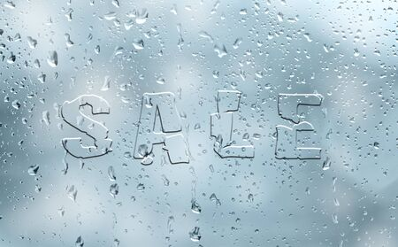 soft sell: Soft blue color seasonal abstract glass effect sale word on wet window with droplets. Creative seasonal sale concept copy space background.
