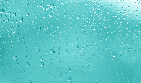 rainy season: Beautiful abstract raindrop pattern on a window. Lovely turquoise colored light window at rainy day. Stock Photo