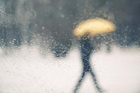 lluvia: Resumen borrosa persona pie cubierto de nieve y lluvia con paraguas amarillo. Vista desde la ventana de vidrios de vehículos de lluvias. Fondo conceptual del mal tiempo.