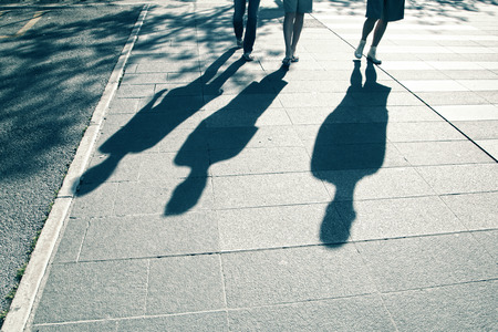 people shadow: People shadows walking on city street on hot summer sunny day. People walking down the street. Blue color tone used. Stock Photo
