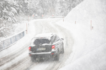 icy conditions: Car on the icy and snowy road during snowfall. Poor road winter conditions for driving.
