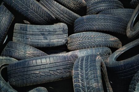 Old used tires stacked with high piles. Grunge filter effect used.