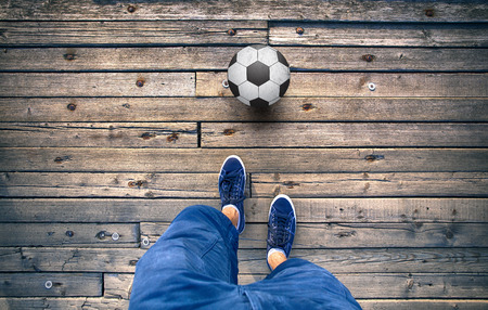 legs: Point of view of a man legs with soccer ball on old wooden tile floor. Stock Photo