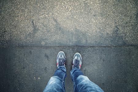 calzado de seguridad: Hombre solo pie en la calle de la ciudad del grunge con textura de asfalto, punto de vista en perspectiva. Peatonal con zapatos de color azul y los pantalones vaqueros que se colocan solamente en el pavimento del grunge. tono de color naranja utilizado.