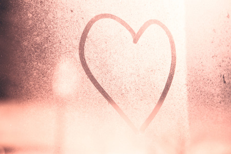 frozen glass: Red color shine abstract blurred love heart symbol drawn by hand on the frozen glass window with soft bright red color background. Selective focus and rose quartz pastel pantone color used.