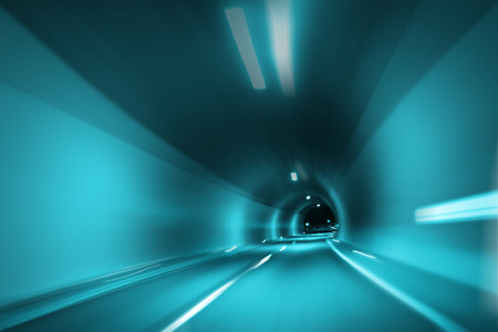 personal perspective: Abstract motion blurred cyan blue colored tunnel lights high speed vehicle driving. Motion blur visualizes the speed and dynamics. Personal perspective used. Stock Photo