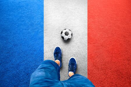 personal point of view: Point of view of a player man legs in blue dress with soccer ball on France flag color soccer field. Concept France football play background. Stock Photo