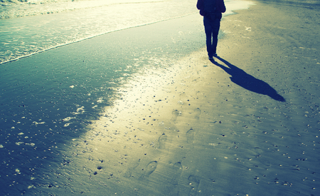 foot prints: Person walking alone on sunny sandy beach with shells, foot prints and sea waves. Lonely walking on sea beach with waves at sunny day.