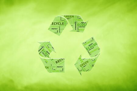 recycle symbol: Creative green color recycle symbol on blurry green background. Recycle symbol containing words related to ecology, environment, ecosystem, nature, etc. Stock Photo