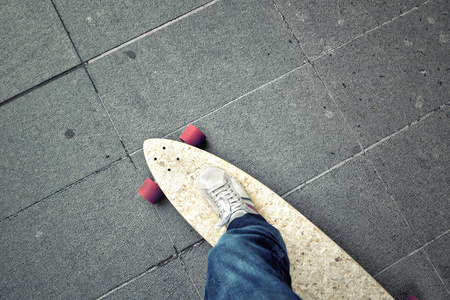 personal perspective: Point of view of a person leg on longboard on the city street. Personal perspective used.
