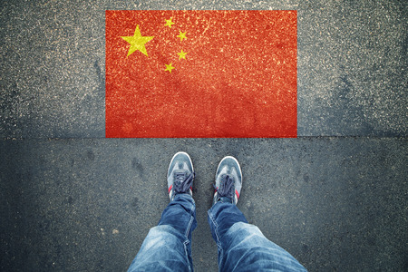 personal point of view: Point of view of a person legs standing in front of China Flag painted on city asphalt street ground.