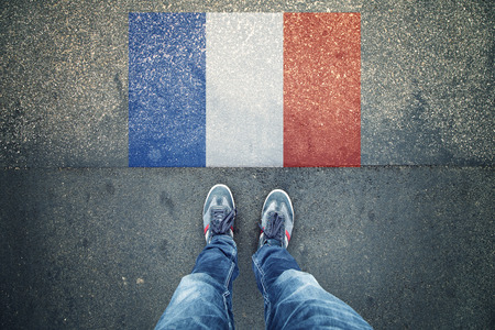 personal point of view: Point of view of a person legs standing in front of France Flag painted on city asphalt street ground.