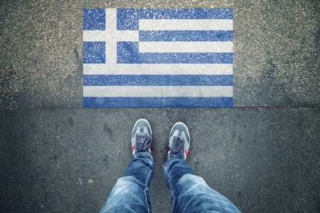 personal point of view: Point of view of a person legs standing in front of Greece Flag painted on city asphalt street ground. Stock Photo