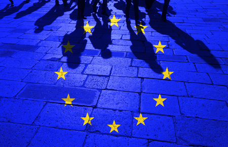 Grunge European Union flag with shadows of the crowd of walking people on stone tiled street floor. Stock Photo