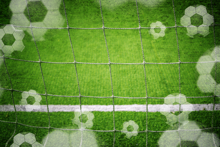 focus on the goal: Soccer goal net closeup with illustrated soccer balls, blurred and textured soccer field background. Grunge filter effect, vignette and selective focus used. Stock Photo