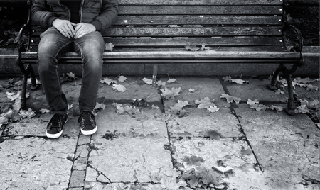 Lonely man sits on a wooden bench in the park with tree leaves on the ground. Single young man with personal problems. Black and white color effect used. Stock Photo