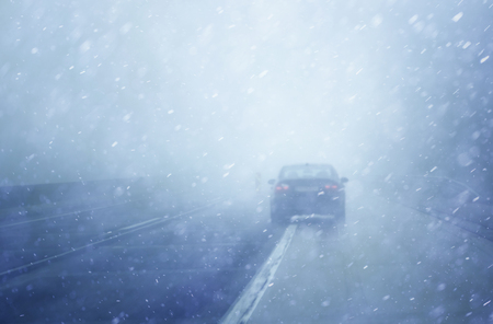driving conditions: Abstract blurred car dangerous highway driving on wet rainy, snowy; and foggy day. Rainy and foggy conditions on the highway. Motion blur visualizes the speed and dynamics.