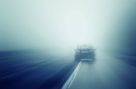 driving conditions: Abstract blurred car high speed driving on wet rainy and foggy highway. Rainy and foggy conditions on the highway. Motion blur illustrates the speed and dynamics.