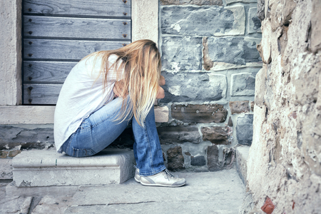 front facing: Sad and lonely blonde women sits in front of a stone aged house. Long hair heartbroken woman facing down alone. Stock Photo